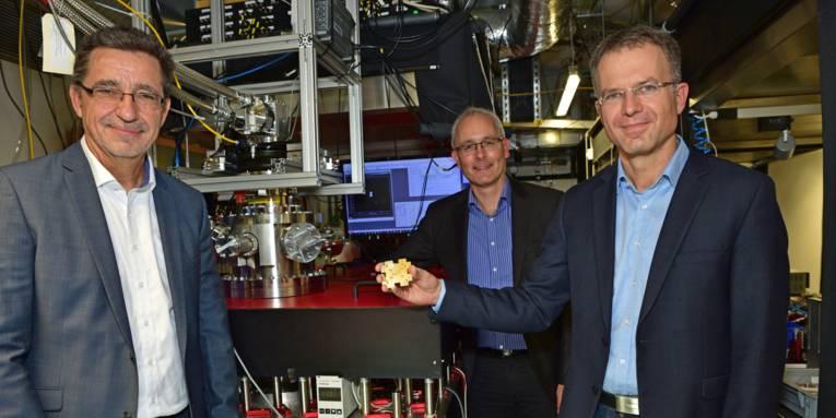Drei Männer in einem mit technischen Geräten befüllten Raum. Einer der Männer hält einen großen Computerchip in den Händen.