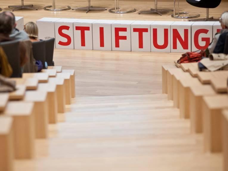 """Das Wort """"Stiftungen"""" in großen Buchstaben vor einer Podiumsbühne"""