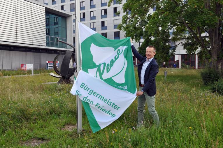 Landrat Thomas Will vom Landkreis Groß-Gerau breitet die Mayors for Peace Flagge aus