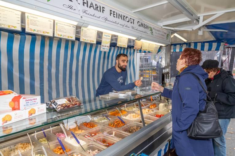 Ein Feinkosthändler bietet einer Kundin Waren zum probieren an.