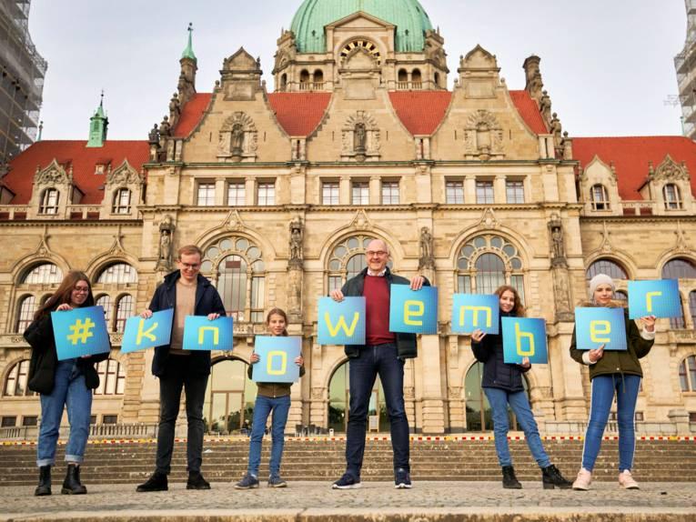 Menschen stehen vor einem historischen Gebäude und halten Tafeln in den Händen, die den Begriff #knowember bilden.