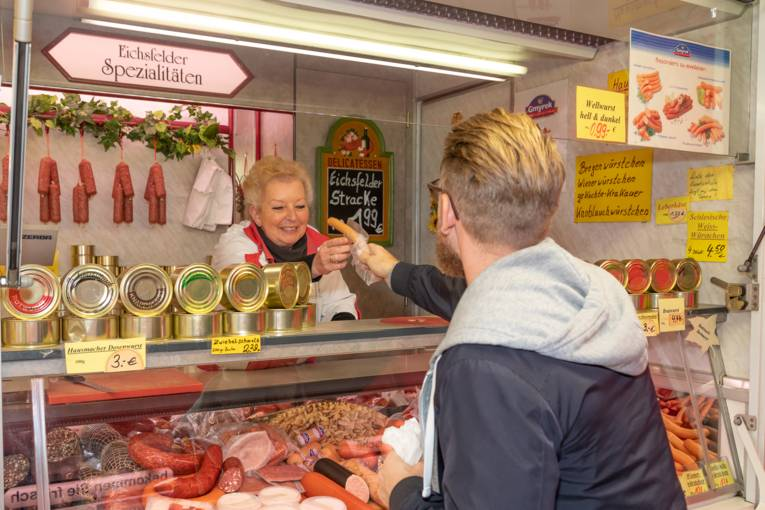Eine Verkäuferin reicht einem Kunden eine Bockwurst.