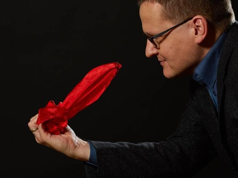 Mann mit kurzem Haar und Brille hält ein gefaltetes Tuch in der Hand.