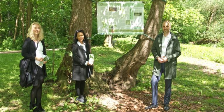 Zwei Frauen und ein Mann vor einem Schild im Wald.