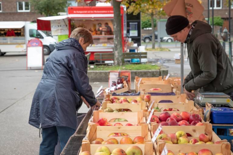 Eine Kundin und ein Verkäufer an einem Stand, an dem frische Äpfel verkauft werden.