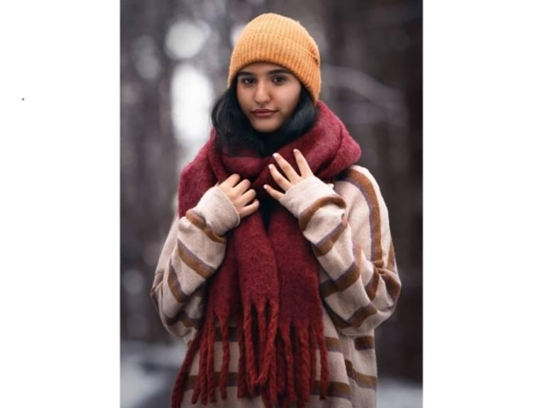 Eine Frau mit Strickpulli, dickem Wollschal und Strickmütze