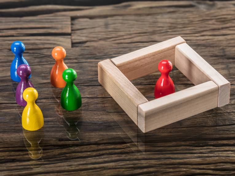 Links stehen bunte Spielfiguren auf einem Tisch. Rechts daneben steht eine Figur in einer anderen Farbe, die durch Holzplatten eingesperrt ist.