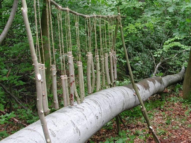Holzstücke hängen in verschiedenen Längen an einem Ast und bilden so ein Xylophon