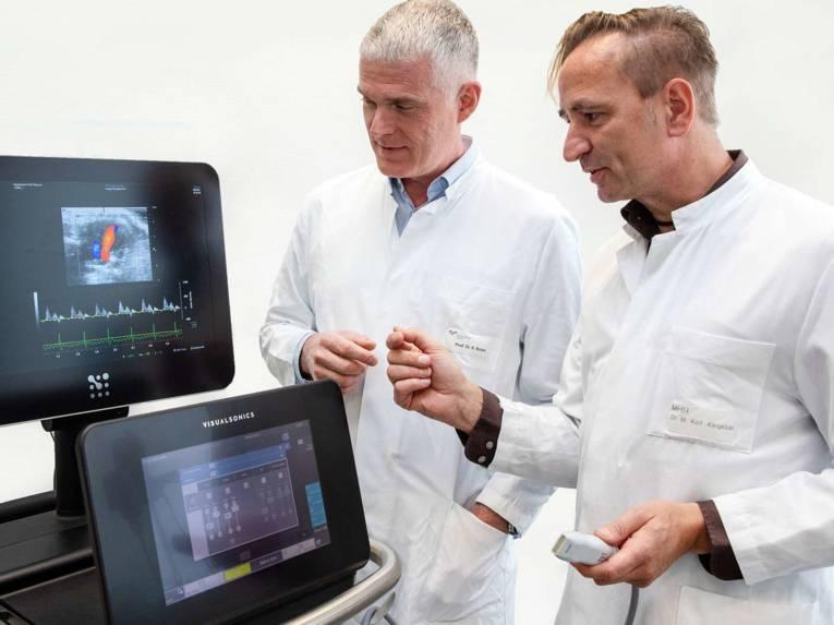 Zwei Männer in Arztkitteln vor zwei Monitoren