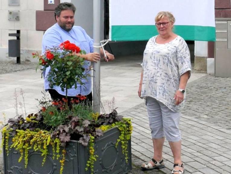 Zwei Personen hängen die Friedensfahne am Rathaus Meiningen auf