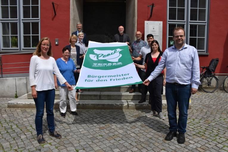 10 Menschen halten die Mayors for Peace Flagge in Greifswald