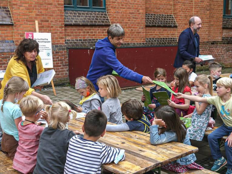 Kinder auf einem Schulhof, die von Erwachsenen Hefte überreicht bekommen.