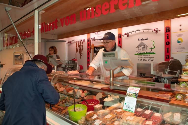 Ein Kunde kauft frische Wurstwaren auf einem Marktstand.