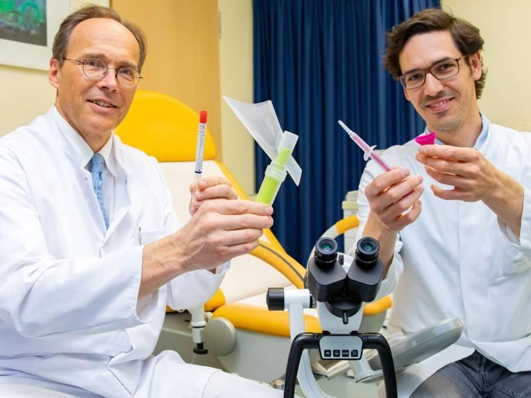 Zwei Männer in weißen Kitteln halten medizinische Geräte in den Händen.