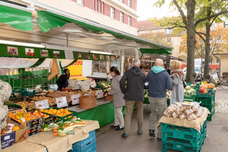 Menschen kaufen Obst und Gemüse an einem Marktwagen.
