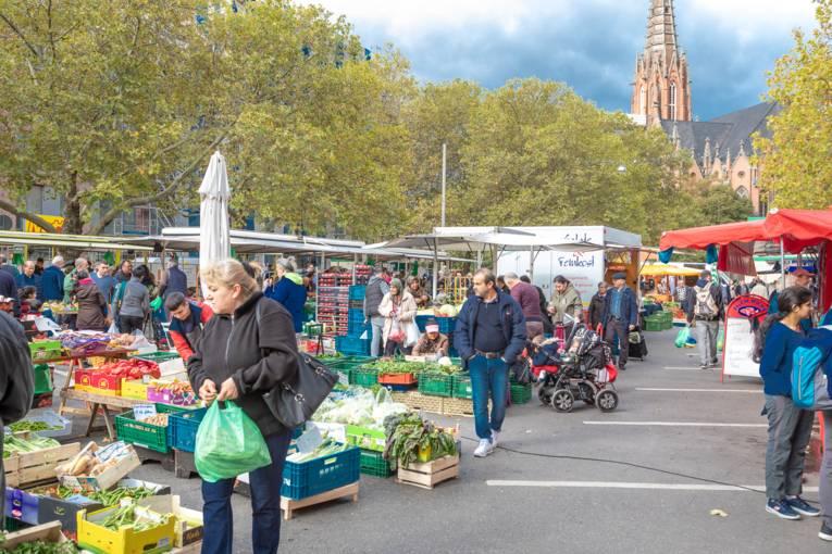 Kundschaft läuft auf dem Wochenmarkt Mitte.