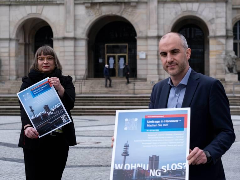 Die Sozialdezernentin und der Oberbürgermeister, die ein Plakat zur Wohnungslosigkeit präsentieren.