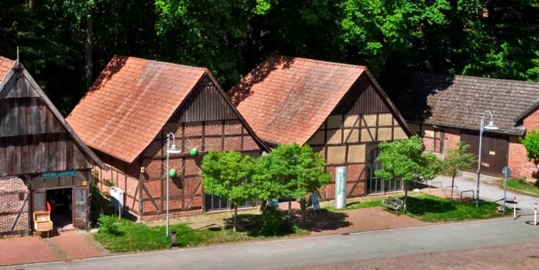"""Zwei Fachwerkscheunen bilden ein großes Gebäude, Schilder weisen auf das """"Infozentrum Steinhude Naturpark Steinhuder Meer"""" hin."""