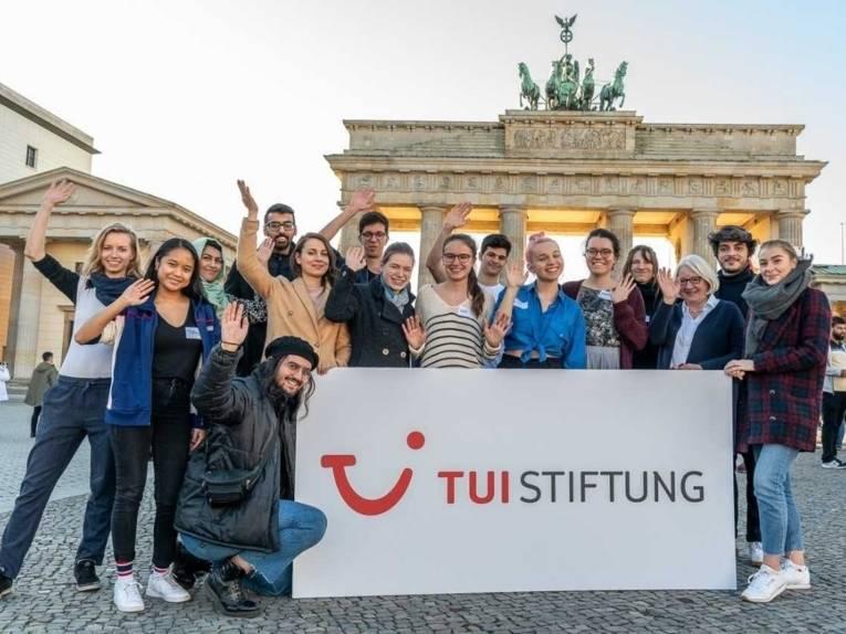 Sechzehn junge Menschen mit einem Plakat mit der Schrift TUI Stiftung vor dem Brandenburger Tor