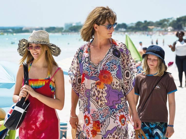 Das Foto zeigt eine Familie die am Strand unterwegs ist. Alle drei Familienmitglieder tragen Bunte Klamotten.
