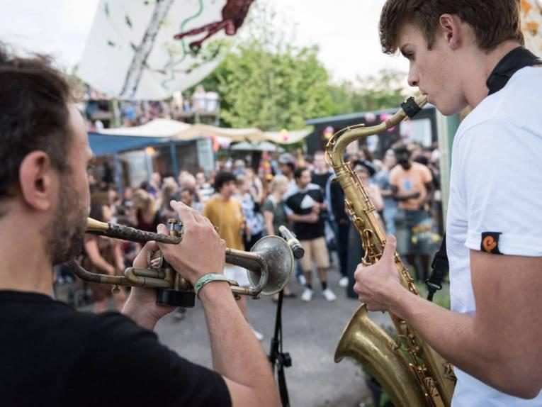 Ein Trompeter und ein Saxofonist spielen vor einer Menschenmenge.