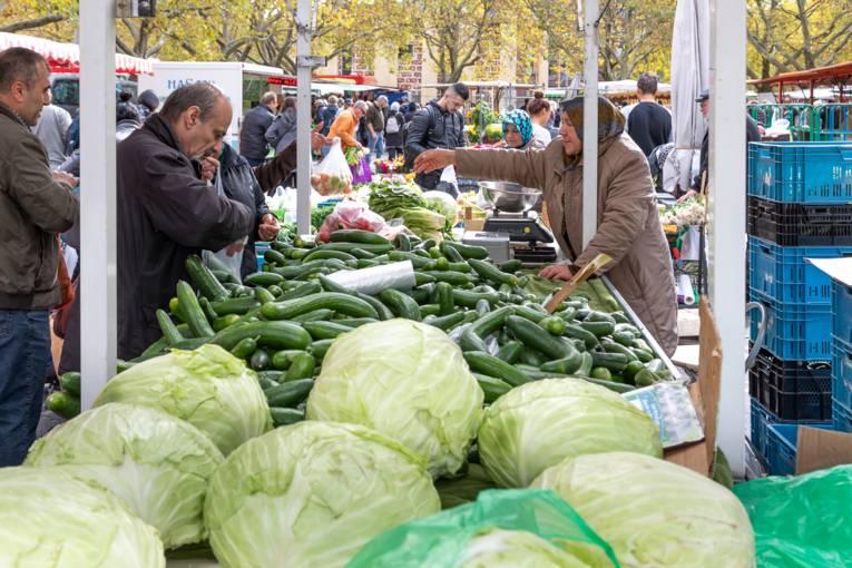 Eine Kundin kauft Gemüse bei einem Händler.