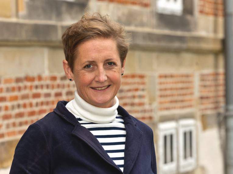Porträtfoto einer Frau. Sandra van de Loo steht draußen neben einem Gebäude und lächelt in die Kamera.