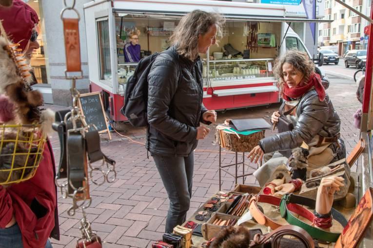 Eine Verkäuferin und eine Kundin an einem Stand für Lederwaren.