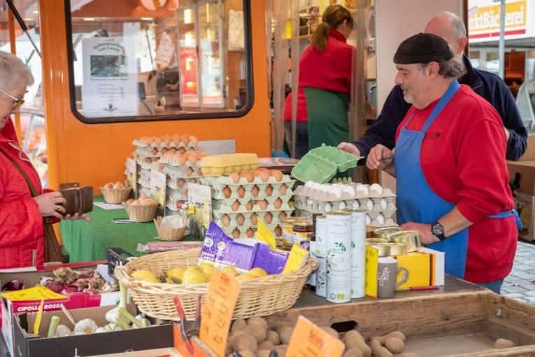 Ein Verkäufer und eine Kundin an einem Stand an dem unter anderem Eier und Gemüse verkauft werden.