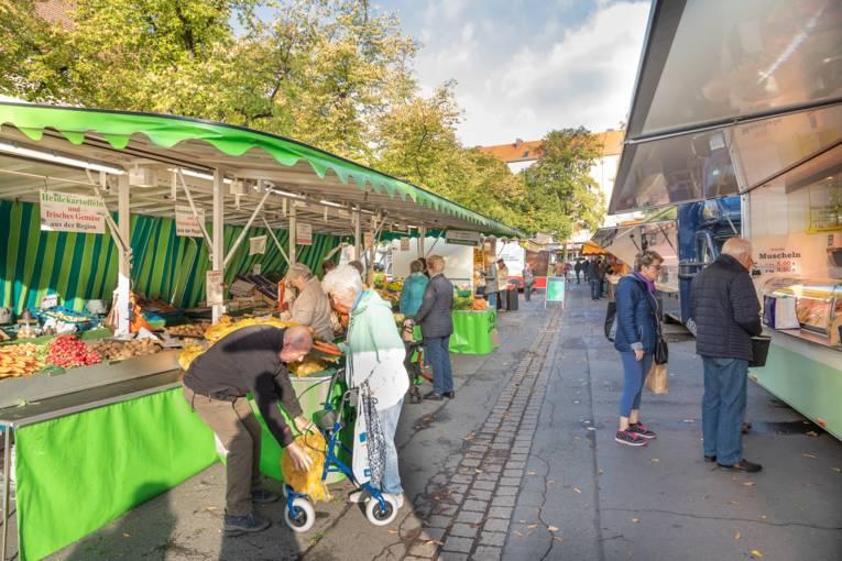 Menschen unterschiedlichen Alters erledigen ihre Einkäufe auf dem Wochenmarkt Schaperplatz.
