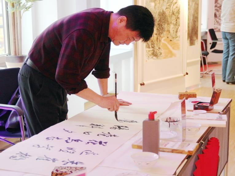 Ein Mann pinselt Schriftzeichen auf einen großen Bogen Papier.