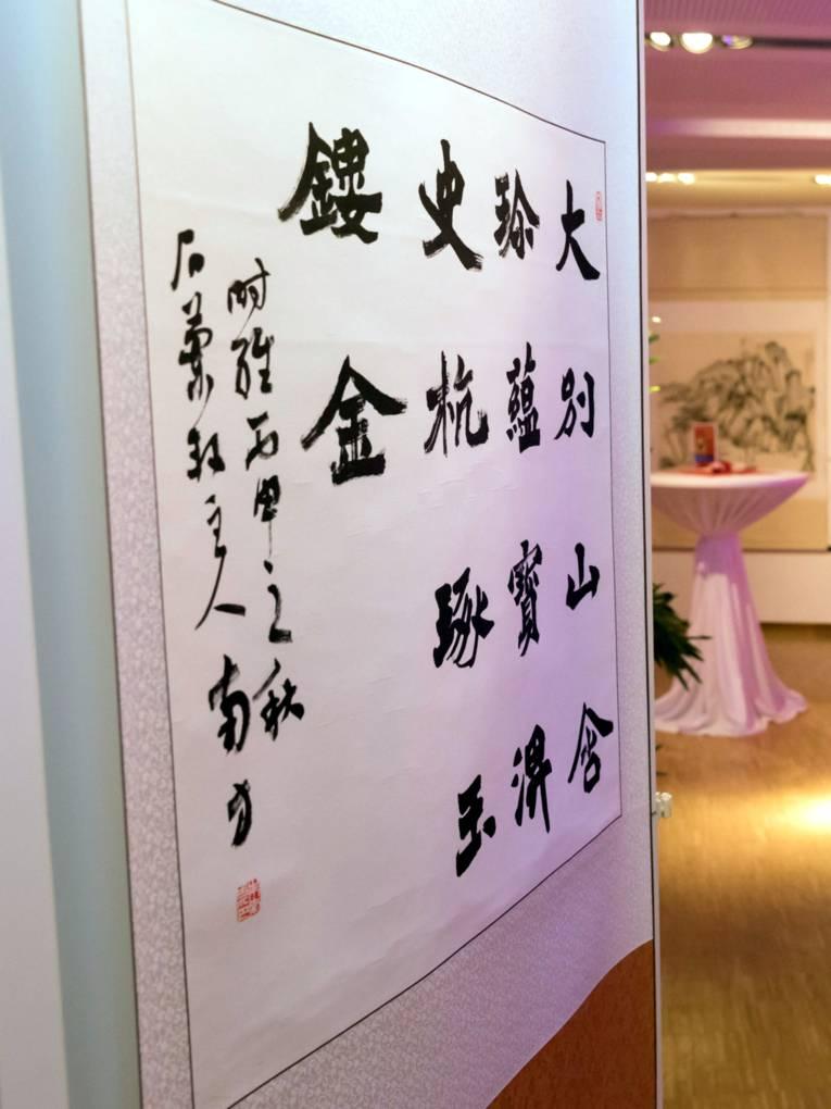 An einer Ausstellungswand hängt ein Papier mit chinesischen Schriftzeichen.