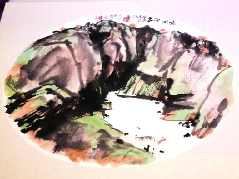 Das Bild zeigt einen Berg an einem Gewässer, am oberen Bildrand sind chinesische Schriftzeichen.