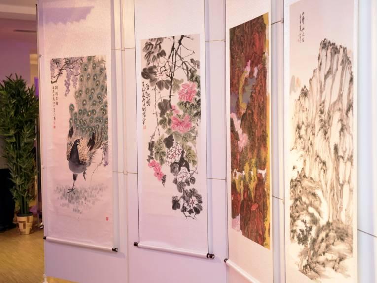 Vier Beispiele chinesischer Malerei hängen an einer Ausstellungswand, die Bilder zeigen einen Pfau, Blüten und zwei Berglandschaften.