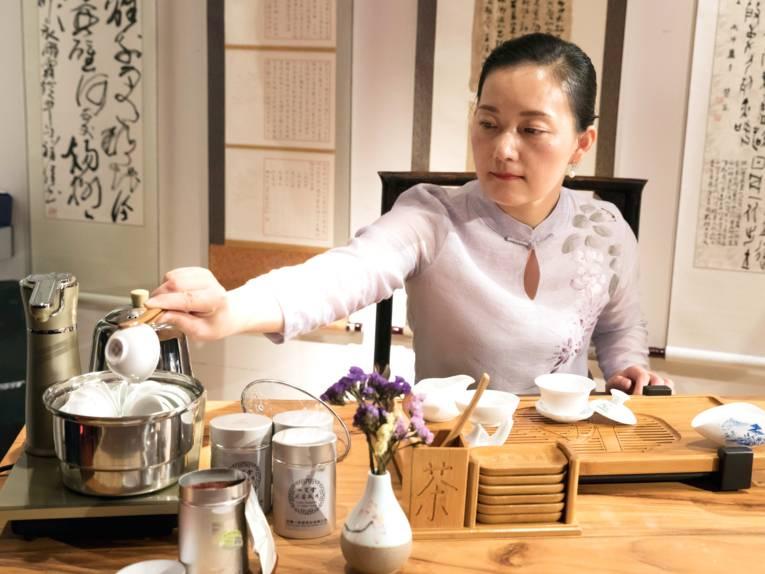 Eine Frau führt eine chinesische Teezeremonie durch.