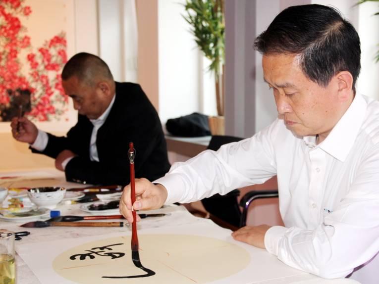 Ein Mann trägt schwarze Farbe mit einem Pinsel auf Papier auf, es entstehen chinesische Schriftzeichen.