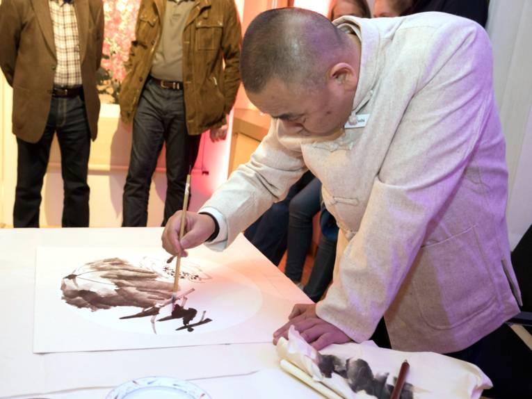 Ein Mann präsentiert ein soeben gemaltes Bild.