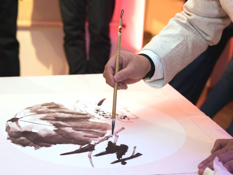 Ein Mann malt mit einem Pinsel auf Papier.