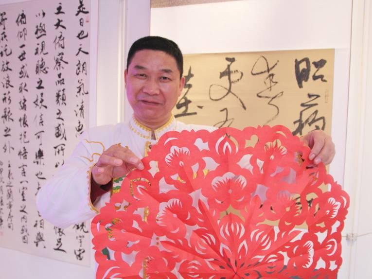 Ein Mann hält einen roten Papierschirm vor die Kamera.