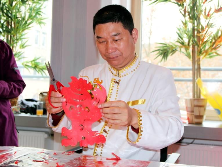Ein Mann bearbeitet Papier mit einer Schere, es entsteht ein roter Hahn.