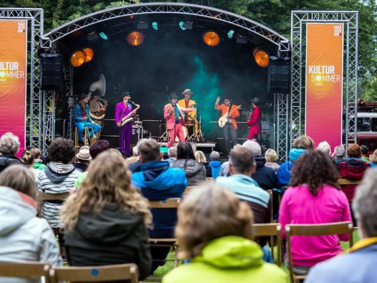 Blick auf eine Freilichtbühne mit Musikprogramm, Publikum sitzt auf Klappstühlen davor.