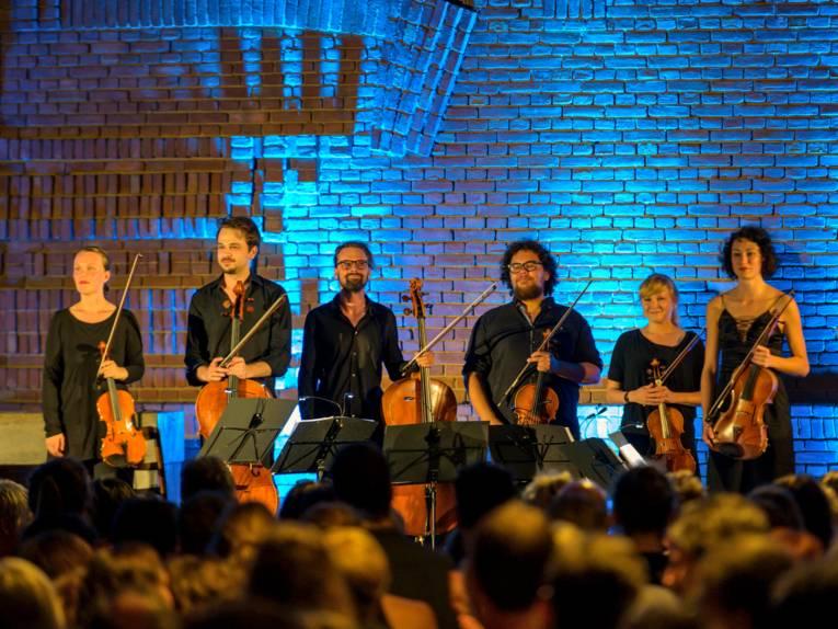 Musikerinnen und Musiker stehen mit ihren Instrumenten vor einem beleuchteten Hintergrund.