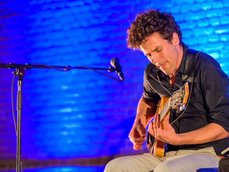 Ein Musiker spielt auf einer Gitarre, der Hintergrund ist blau.