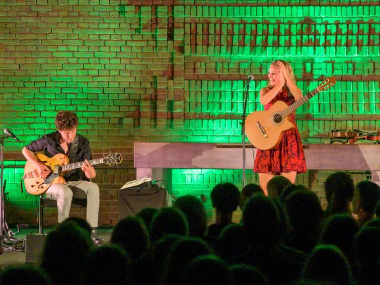 Ein Musiker und eine Musikerin stehen mit Gitarran auf einer grün beleuchteten Bühne.