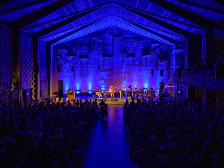 Blick von den hinteren Reihen einer Kirche hin zu einer blau beleuchteten Bühne.