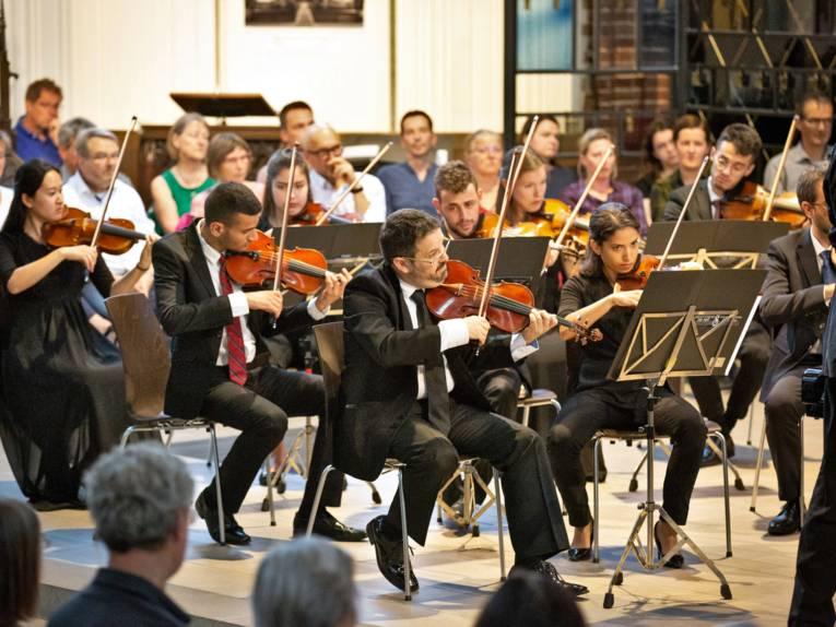 Musikerinnen und Musiker spielen auf Streichinstrumenten.