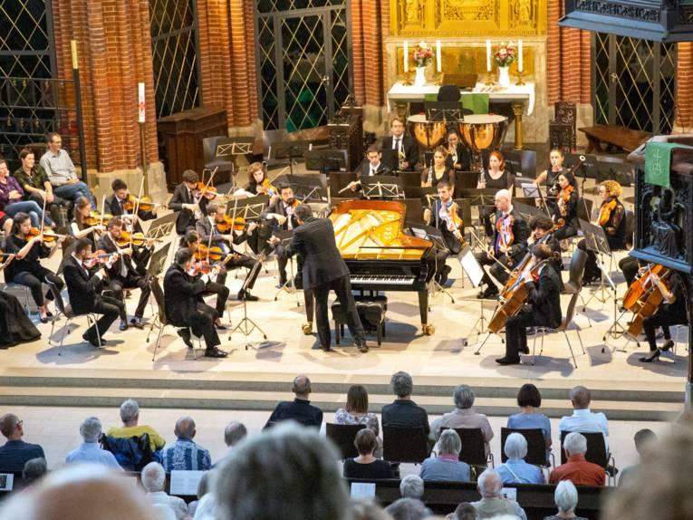 Blick aus den Reihen der Zuschauerinnen und Zuschauer auf ein Orchester, das in einer Kirche auftritt.