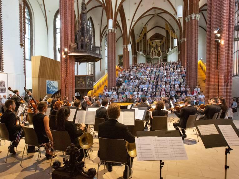 Blick über die Schulter der Musikerinnen und Musiker auf das Publikum in der Kirche während des Auftritts.