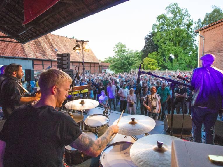 Blick von einer Bühne über die Schulter des Schlagzeugers während eines Konzertes auf das Publkum.