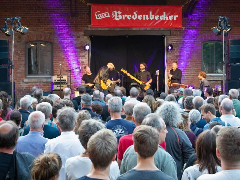 Publikum verfolgt den Auftritt einer Band auf einer Bühne im rustikalen Ambiente einer Scheune.